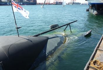 2017-11-04 1427 Stern of submarine, with flag, and harbour race behind.JPG
